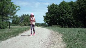 Girl walks while using smartphone stock video footage