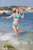 Girl walks in water along shore Royalty Free Stock Photo