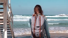 Girl walks by white stairs to sunny sea shore. Freedom. Hair blowing in wind. Woman with backpack on beach. Slow motion. stock video footage