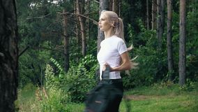 A girl walks through the woods with a pic: Active way of life stock footage