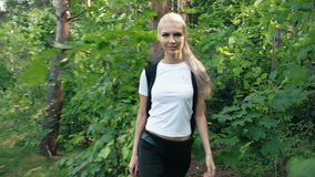 A girl walks through the woods with a pic: Active way of life stock video