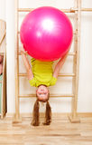 Girl on wall bars. Elementary aged girl hanging on wooden wall bars with a large gymnastic ball Royalty Free Stock Photo