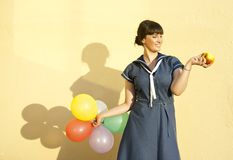 The girl  of the wall keeps apple and balloons Royalty Free Stock Image