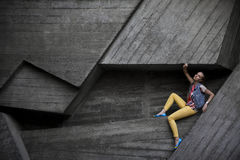The girl at the wall. In yellow pants Royalty Free Stock Photography