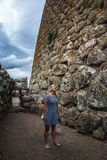 Girl wandering in ancient ruins in Sardinia, Italy. Nuraghe Lose in Sardinia, Italy.  Nuraghic sites are archaeological remnants of prehistoric building of Stock Image