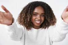 Girl wanna warm hugs. Tender and cute african-american female in sweater extending hands towards camera to cuddle and stock photography