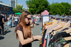 Girl want to buy dress on the street flea market Royalty Free Stock Images
