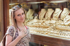 Girl Wants Jewelry. Pretty young girl standing in front of jewelry shop and wishes to buy it or looking at her boyfriend to buy it for her Stock Photos