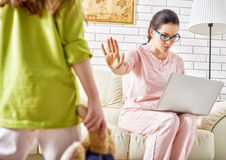 Girl wants to play. Сhild girl wants to play with mother, but she works at the computer Royalty Free Stock Images