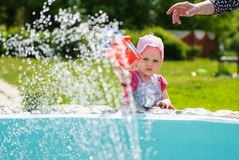 Girl wants to pour a bucket of water from a fountain Royalty Free Stock Photos