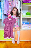 Girl  in the wardrobe. Happy girl with violet dress in her hand Royalty Free Stock Images