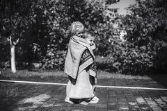 Girl warm boy with a towel(blck white) Stock Photos