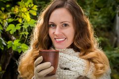 Girl in warm clothes on autumn park holding a cup with hot bever stock photography