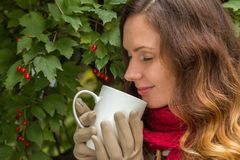 Girl in warm clothes dreaming on autumn park with cap of hot tea royalty free stock images