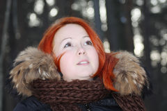 Girl in warm clothes looks up in forest at winter Royalty Free Stock Photography