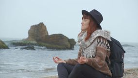 Girl in warm clothes relax on the shore of the Sea on a cool autumn day.  stock footage