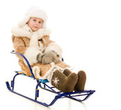 The girl in warm clothes sits on a sled Royalty Free Stock Photo