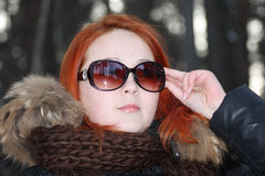 Girl in warm clothes and sunglasses looks away Royalty Free Stock Photo