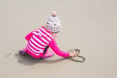 Girl in warm clothing drawing heart shape on sand at beach Stock Photo