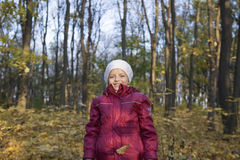 Girl In Warm Clothing Under Falling Leaves. Portrait of a smiling girl in warm clothing under falling leaves in park royalty free stock photo