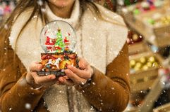 Girl in warm coat holding glass ball with firtrees, house and artificial snow in a mall at the Christmas Fair. Winter mood stock photography