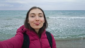 A girl in a warm jacket makes a selfie on the beach in windy stormy weather. Big wave. Girl showing tongue at the camera, boasting royalty free stock photography