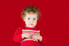 Girl in a warm knitted sweater on red background Royalty Free Stock Photos