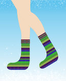 Girl in warm knitted woolen socks on winter background Royalty Free Stock Image