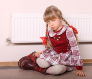 Girl warm  near radiator.  Crisis. Stock Images