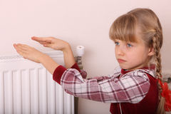 Girl warm one's hands near radiator Royalty Free Stock Image