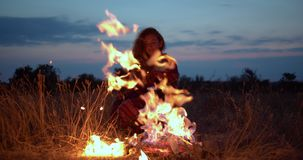 The girl in a warm plaid sitting by the fire in the evening. stock video footage