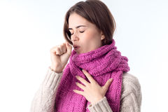 Girl in a warm scarf coughs closing eyes is isolated on  white background Stock Images