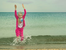 The girl in a warm suit plays in the cold sea. Royalty Free Stock Image