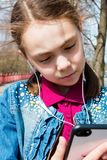 Girl in warm sunny weather on the street with headphones listening to music in the gadget close-up stock photography