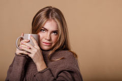 Girl in warm sweater drinking a warm beverage from a mug. Royalty Free Stock Images