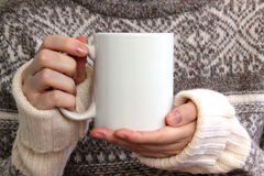 Girl in a warm sweater is holding white mug in hands.