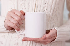 Girl in warm sweater is holding white mug in hands.