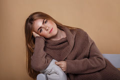 Girl in a warm sweater leaning on the arm of the sofa. Royalty Free Stock Image