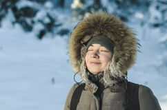 Girl in warm winter jacket with a hood with fur, eyes closed, smiling, enjoying the beautiful weather.  Royalty Free Stock Photos