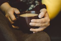 Hands with hot drink. Girl with a warming drink in hand lying on the sofa with a blanket Royalty Free Stock Photos