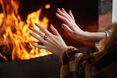 Girl is warming her hands by the fire. In the fireplace. young woman by the fire Royalty Free Stock Photos
