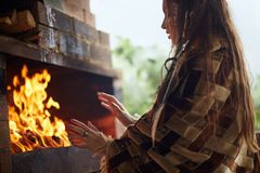 Girl is warming her hands by the fire. In the fireplace. young woman by the fire Royalty Free Stock Photo