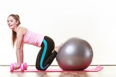 Girl warming up with ball and dumb bell weights. Exercise sport fitness health concept. Fit girl exercising. Attractive female warming up with ball and dumb Royalty Free Stock Images
