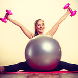 Girl warming up with ball and dumb bell weights. Exercise sport fitness health concept. Fit girl exercising. Attractive female warming up with ball and dumb Stock Image