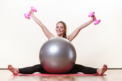 Girl warming up with ball and dumb bell weights. Exercise sport fitness health concept. Fit girl exercising. Attractive female warming up with ball and dumb Royalty Free Stock Photo