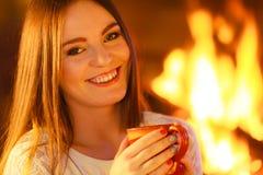 Girl warming up at fireplace holds mug Stock Photography