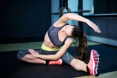 Girl warming up before weight training in the gym, toned