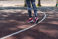 Girl warming up before a workout. The girl is Jogging in the Park Royalty Free Stock Photography