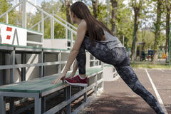 The girl warming up before a workout. The girl warming up before training on a bench in the Park Stock Image
