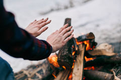 Girl warms hands near a fire in winter Stock Photo